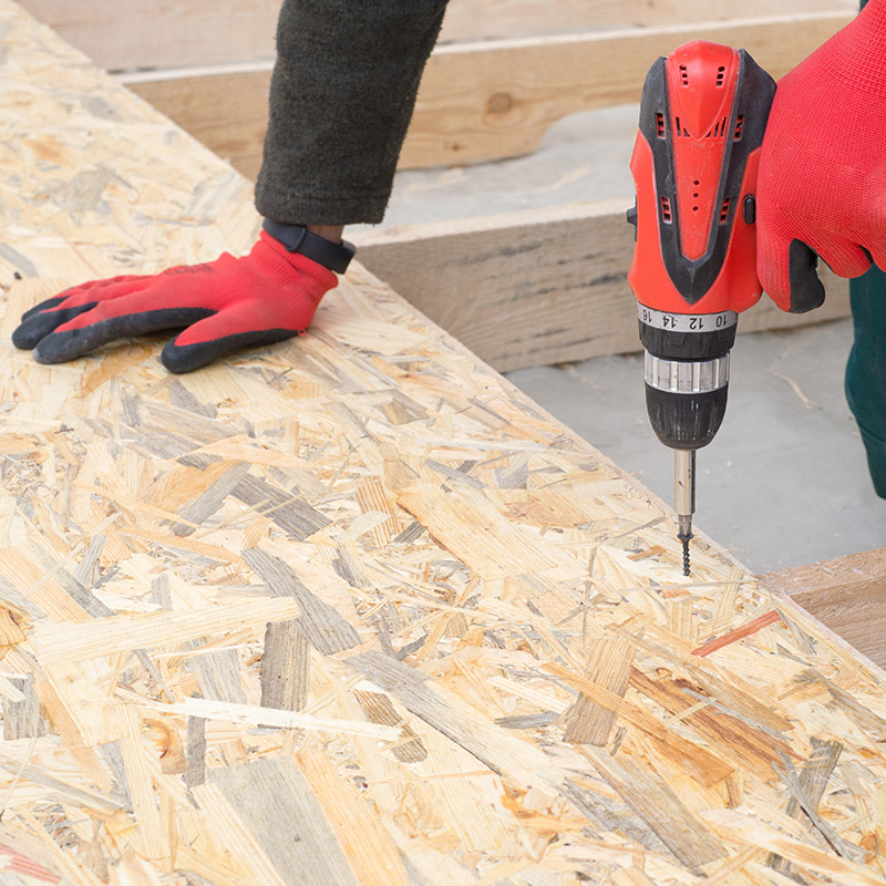 Man worker screws wooden oriented stands bords on insulated floo
